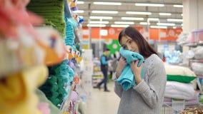 Textiel voor huis De jonge donkerbruine vrouw kiest een handdoek in de opslag stock videobeelden