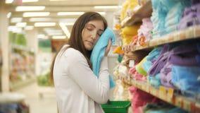Textiel voor huis De jonge donkerbruine vrouw kiest een handdoek in de opslag stock video