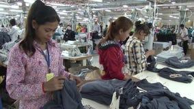 Textielkledingstukfabriek: De vrouwelijke werknemers sorteren voltooide kledingstukken stock videobeelden