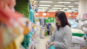 textil En ung kvinna väljer en handduk i ett lager för hem- produkter stock video
