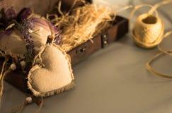 Textil hjärta bredvid en trägåvaask arkivbild