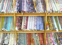 Textile. Rolls of cloth patterns in shelves Royalty Free Stock Images