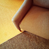 Textile armchair and knitted carpet in warm colors Stock Photography