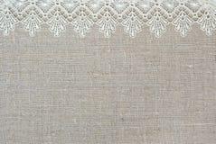 Textile background. Lace border over unpainted burlap stock photo