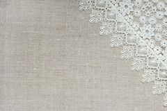 Textile background. Lace border over unpainted burlap royalty free stock photography
