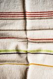 Textile background with a multicolored striped linen napkin, top view. Natural textile background. Fabric texture background. Text. Ure of natural linen fabric royalty free stock photo