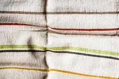 Textile background with a multicolored striped linen napkin, top view. Natural textile background. Fabric texture background. Text. Ure of natural linen fabric royalty free stock images