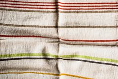 Textile background with a multicolored striped linen napkin, top view. Natural textile background. Fabric texture background. Text. Ure of natural linen fabric stock photos