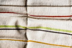 Textile background with a multicolored striped linen napkin, top view. Natural textile background. Fabric texture background. Text. Ure of natural linen fabric stock image
