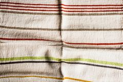 Textile background with a multicolored striped linen napkin, top view. Natural textile background. Fabric texture background. Text. Ure of natural linen fabric stock photo