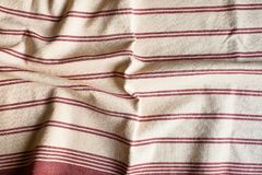 Textile background with a red striped linen napkin, top view. Natural textile background. Fabric texture background. Texture of na. Tural linen fabric royalty free stock photos