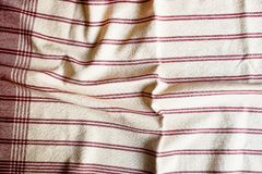 Textile background with a red striped linen napkin, top view. Natural textile background. Fabric texture background. Texture of na. Tural linen fabric stock image