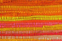 Textile background. In red, yellow, orange, pink and green manually weaved Royalty Free Stock Images