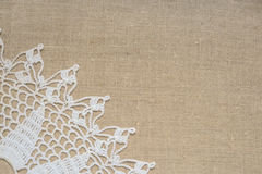 Textile background. White lace border over burlap royalty free stock images