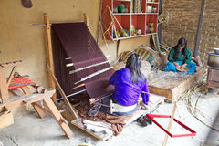 Textile of Bhutan. Bhutanese woman is working at vertical loom, Thimphu, Bhutan. Textile of Bhutan represent a rich and complex repository of a unique art form royalty free stock images