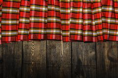 Textile in a cage and wood texture. Black wooden table. Cloth in a cage on a black wooden texture. Colorful fabric on the table. V. Iew from Stock Image