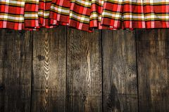 Textile in a cage and wood texture. Black wooden table. Cloth in a cage on a black wooden texture. Colorful fabric on the table. V. Iew from Royalty Free Stock Photos
