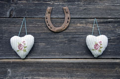 Textile cloth hearts on wooden wall and horseshoe Royalty Free Stock Photography