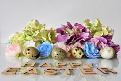 Textile Flowers, Quail Eggs and Lettering Happy Easter on the white Background. Textile Roses and Hydrangeas, Quail Eggs and Lettering Happy Easter on the white stock photos