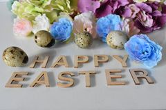 Textile Flowers, Quail Eggs and Lettering Happy Easter on the white Background. Textile Roses and Hydrangeas, Quail Eggs and Lettering Happy Easter on the white stock photography