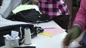 Textile Garment Factory: Female garment workers sort completed garments
