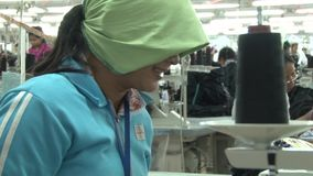 Textile Garment Factory: MCU green scarfed worker smiling, working stock video footage