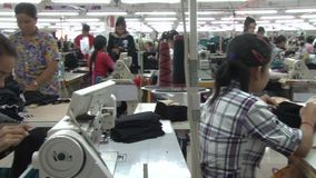 Textile Garment Factory: MS worker at station 1, pan to station 2 Workers stock video