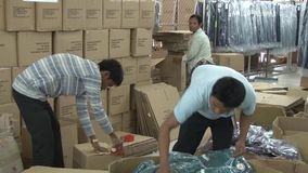 Textile Garment Factory: Two male workers pack completed garments in boxes stock video footage