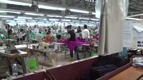 Textile Garment Factory Workers: MS pan from worker bundling to factory floor stock video footage