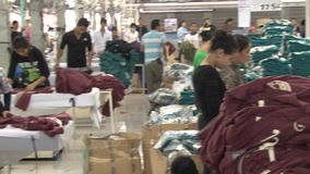 Textile Garment Factory Workers: WS of factory floor, pan to workers ironing stock video