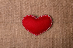 Textile heart on fabric texture of burlap Stock Photography
