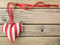 Textile heart with red ribbon Stock Images