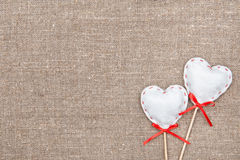 Textile hearts on the burlap. Background stock image