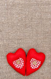 Textile hearts on the burlap. Background stock photography