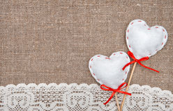 Textile hearts and lacy cloth on the burlap. Background stock images