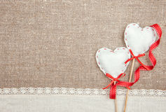 Textile hearts, ribbon and linen cloth on the burlap. Background stock photography