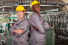 Textile industrial technicians. Two textile industrial technicians portrait in factory royalty free stock photos