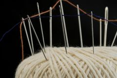 Needles and orange cotton thread on a white cotton tread ball macro closeup. Textile materials details, needles and colored threads on a white cotton thread ball Royalty Free Stock Photos