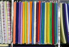 A textile multicolored wrapped raw cloth bundles in rack stand used to make finished products royalty free stock image