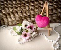 Textile pink heart, flower and necklace on brown wickered background. Card for Valentine's day Stock Photo
