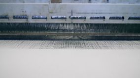 Textile plant machine weaves white fabric automatically. Textile factory equipment in work. Textile plant machine weaves white fabric automatically. 4K stock footage