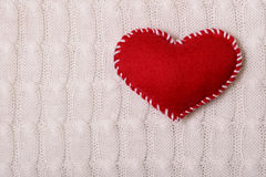 Textile red heart on a knitted texture Stock Photography