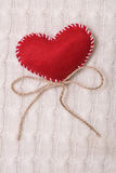 Textile red heart on a knitted texture Stock Image
