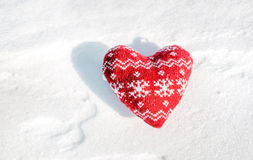 Textile red heart with snow flakes on the snow Stock Photos
