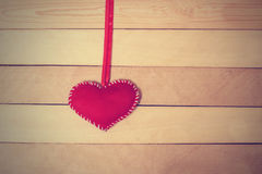 Textile red heart  on the tape on a wooden texture Royalty Free Stock Photo