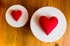 Textile red hearts on gift boxes. On wooden background Stock Photography