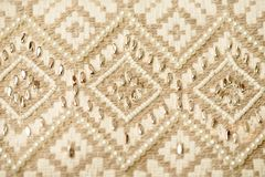 Textile with rhomb pattern embroidery. Beige textile with rhomb pattern embroidery stock image