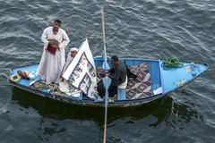 Textile salesmen in their rowing boat near the Esna Lock on the River Nile in Egypt. Textile salesmen in their rowing boat display their goods for sale to Stock Photos