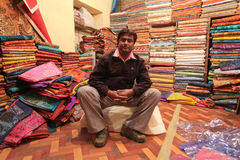 Textile shop owner. JAISALMER – DECEMBER 2010 : Indian man posing in his textile shop in center of Jaisalmer, India on December 10. 2010. Price of cotton Stock Image