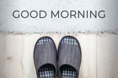 Textile slippers on wooden floor with white fur rug. Good morning concept royalty free stock photos